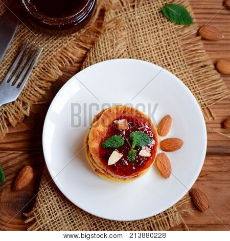 Tasty homemade cottage cheese pancakes. Easy cottage cheese pancakes with berry jam and nuts. Top view