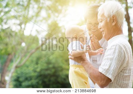 Grandparents holding baby grandson at outdoor park, Asian family, life insurance concept.