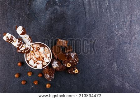 A cup of hot chocolate with marshmallows and marshmallows in chocolate on a stick and a cupcake with hazelnuts, chunks of chocolate