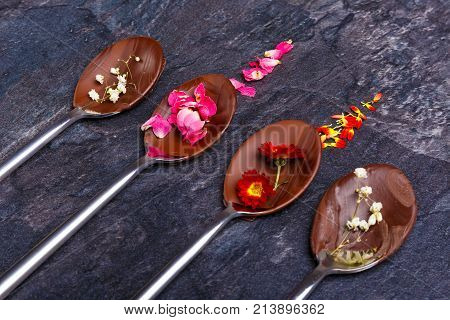 Spoons with frozen chocolate and flowers with petals next to the spoons in them lie in a row