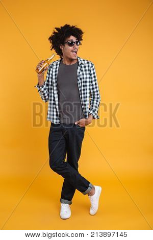 Full length portrait of a smiling happy african man in sunglasses holding beer bottle while standing and looking away isolated over orange background