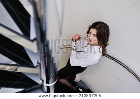 Beautiful young sexy girl in a strict office suit and wearing glasses on the background of a staircase