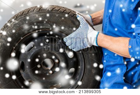 car service, repair, maintenance and people concept - close up of auto mechanic man changing tire at workshop over snow