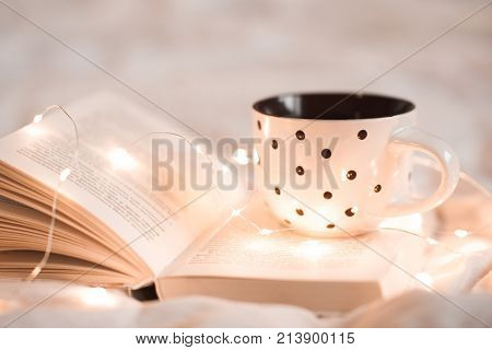 Cup of tea staying on open book with Christmas lights in bed closeup. Good morning. Breakfast time.
