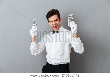 Portrait of a cheerful happy male waiter dressed in unifrom holding bunch of money banknotes isolated over gray background