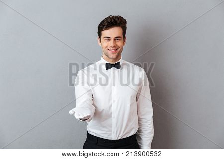 Portrait of a smiling friendly male waiter dressed in unifrom standing with outstretched hand isolated over gray background
