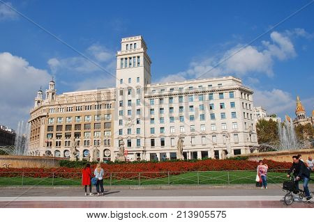 BARCELONA, SPAIN - NOVEMBER 1, 2017: People walk in the historic Placa de Catalunya. The flagship store of casual clothing brand Desigual is in the background.