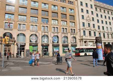 BARCELONA, SPAIN - NOVEMBER 1, 2017: People walk in the street in the historic Placa de Catalunya. The flagship store of casual clothing brand Desigual is in the background.