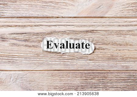 Evaluate of the word on paper. concept. Words of Evaluate on a wooden background.