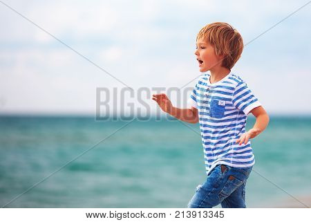 Cute Young Boy, Kid Running Along The Seaside, Summer Beach