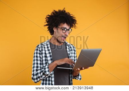 Portrait of an excited young african man in eyeglasses using laptop computer isolated over orange background