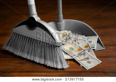 Broom sweeping dollars into dustpan