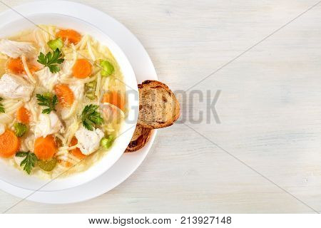 An overhead closeup photo of a plate of chicken, vegetables, and noodles soup, shot from above on a light wooden texture with slices of bread and a place for text