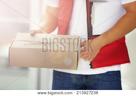 Delivery man in uniform holding parcel indoors