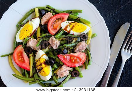 Summer warm salad with cooked green beans tuna tomatoes boiled eggs and sauce balsamico glassa in white plate with knife and fork on black stone background. Healthy eating concept. Top view.