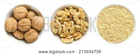 Whole walnuts, kernel halves and ground walnuts in white bowls on white background. Seeds of the common walnut tree Juglans regia, used as snack or for baking. Macro food photo close up from above.