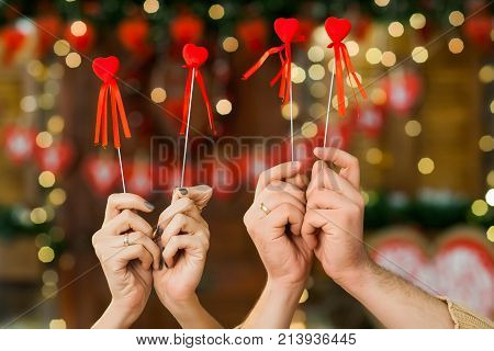 Close up shot boy and girl holding hearts in hands on valentine's day. Only hands with hearts over valentines day decoration