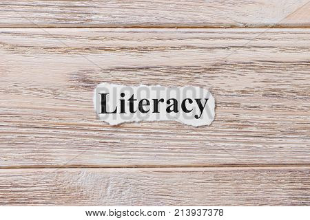 LITERACY of the word on paper. concept. Words of LITERACY on a wooden background.
