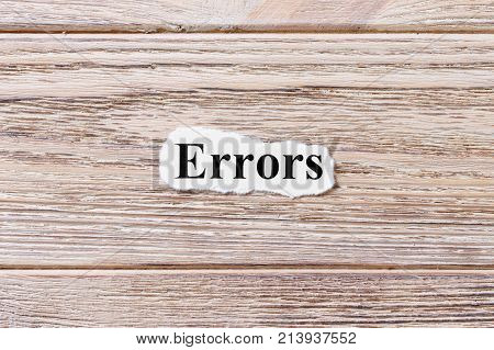 Errors of the word on paper. concept. Words of Errors on a wooden background.