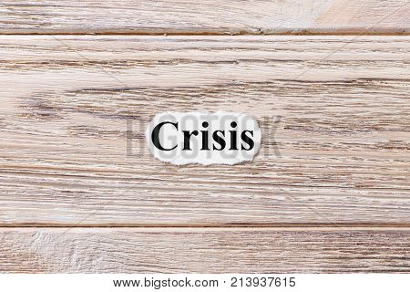 CRISIS of the word on paper. concept. Words of CRISIS on a wooden background.