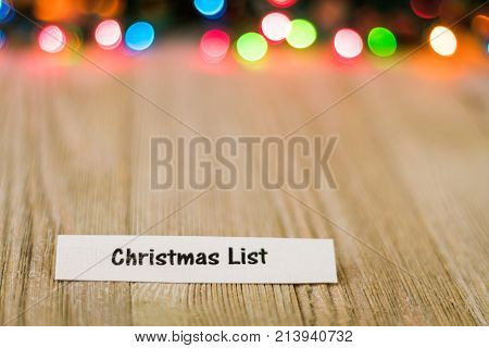 Christmas List Concept on wooden board and colored lights, selective focus, room for copy