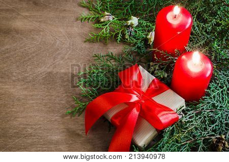 Christmas background with fir tree burning candles and present on wooden board. Advent time. Toned image Copy Space