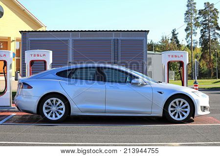 TOIJALA FINLAND - SEPTEMBER 24 2017: Silver Tesla Model S fully electric car charges battery at Tesla Supercharger charging station in Toijala Finland.