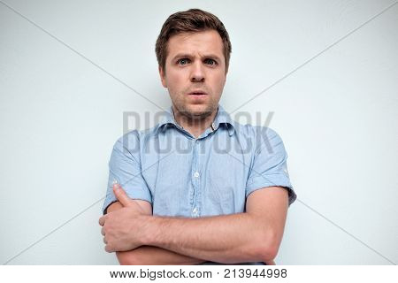 Confused caucasian man looking at camera with fear in his eyes, crossing hands on chest