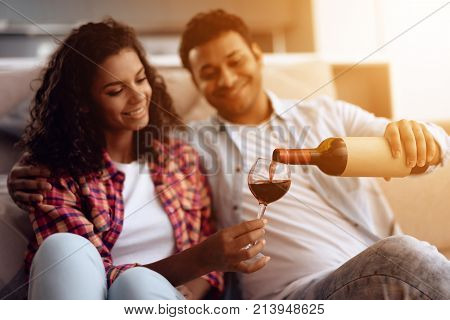 Black man and woman are sitting on the couch. A man and a woman embraced and drank wine. They are happy. They rest after a hard day's work.