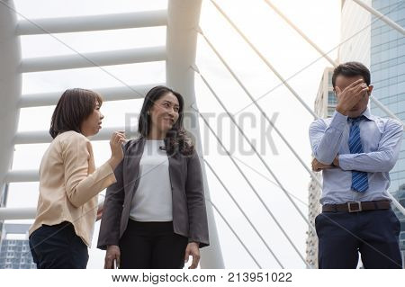 Outdoors portrait of two employees gossiping about boss/rumor and gossip concept
