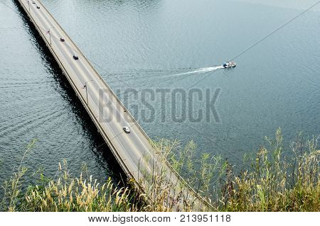 Boat Passing Under A Bridge Over The River