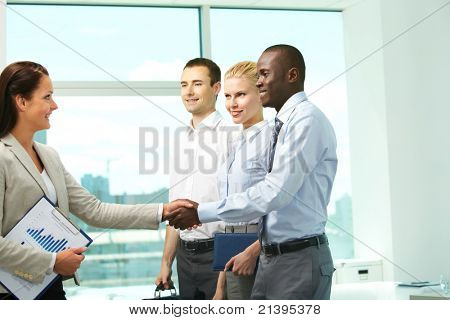 Image of two successful associates handshaking with partners near by