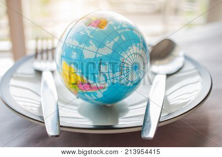 Globe model placed on plate with fork menu in famous hotels. International cuisine is cuisine that is practiced around the world often associated with specific region country.