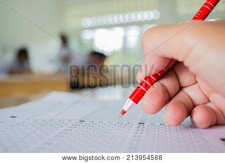 Students hand testing doing examination with pen drawing selected choice on answer sheets in school exams blur pupils college backgroud. Education system tests concept.