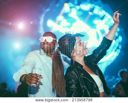 Young friends dancing at party in night club - Diverse culture people enjoying weekend nightlife with original laser lights colors in background - Youth concept - Soft focus on black man - Warm filter