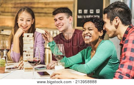 Young Students playing board game at hostel living room - Diverse culture people having fun and drinking wine at pub restaurant - Friendship and alternative evenings concept - Focus on afro girl face