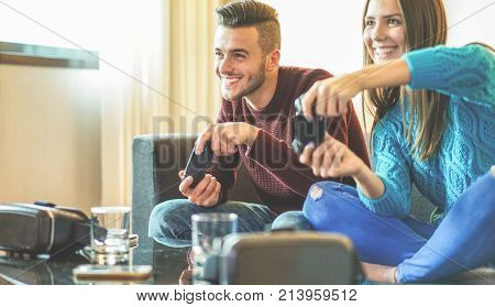 Happy friends playing video games - Young people having fun with new technology console online - Happiness and gaming concept - Soft focus on man face - Warm filter