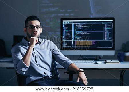 Indian professional programmer sitting at his table with big monitor
