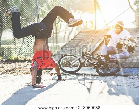 Biker man making video feed of his breakdancer friend dancing in city park outdoor - Young people having fun outdoor sharing media online - Focus on left man - Youth trend and friendship concept