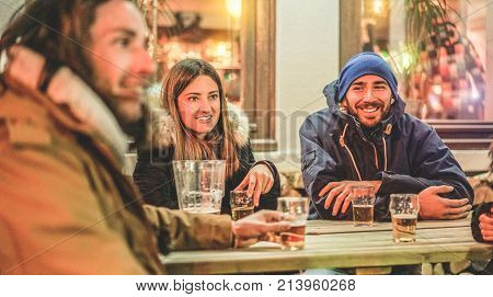 Happy friends toasting beers at chalet pub restaurant in mountains on evening time - Rich people having fun in winter vacation - Friendship and youth concept - Soft focus on woman face - Warm filter
