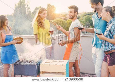 Happy friends cooking bbq meat and drinking wine on top of the roof at barbecue party - Young people preparing dinner outdoor - Focus on two center guys - Food fun and friendship concept
