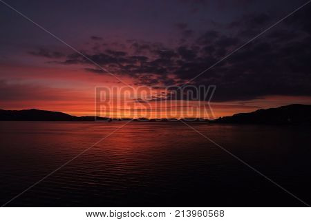 Night seascape in Bergen Norway. Sea or ocean water under dark magenta sky on natural background. Nature ecology wanderlust vacation concept