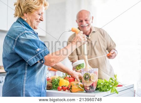 Happy senior couple preparing healthy vegetarian breakfast with fruits and vegetables - Old cheerful people taking care about diet - Healthvegan and organic concept - Focus on woman face