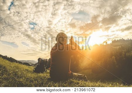 Young man doing yoga meditation at sunset mountains - Nature travel healthy lifestyle and relax concept - People harmony with nature - Focus on body silhouette