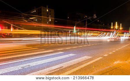car light trails on the street near road bridge people walking in fast motion night street background