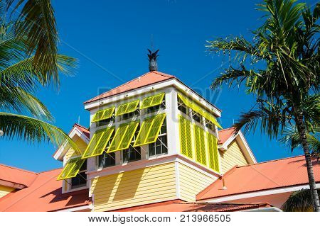 Mansard with open yellow window shutters and pineapple on terracotta roof on sunny day on blue sky in Nassau Bahamas. Architecture building structure design. Summer vacation concept Hotel atlantis