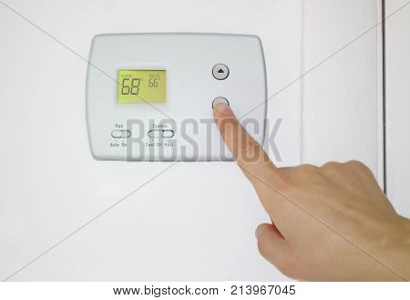 Person adjusting the temperature on a wall thermostat
