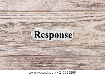 RESPONSE of the word on paper. concept. Words of RESPONSE on a wooden background.