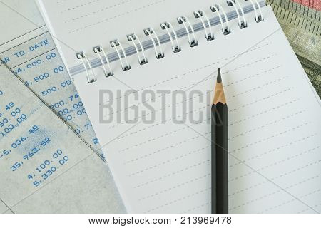 Financial salary man concept as pencil on white notebook with carbon salary slips.