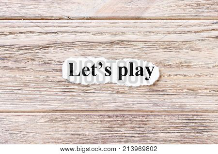 lets play of the word on paper. concept. Words of lets play on a wooden background.